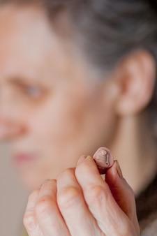 Mulher, inserindo o aparelho auditivo no ouvido