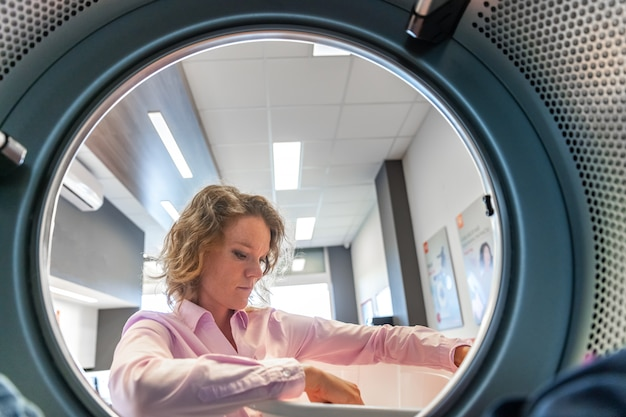 Mulher inserindo roupas em uma secadora em uma lavanderia pública