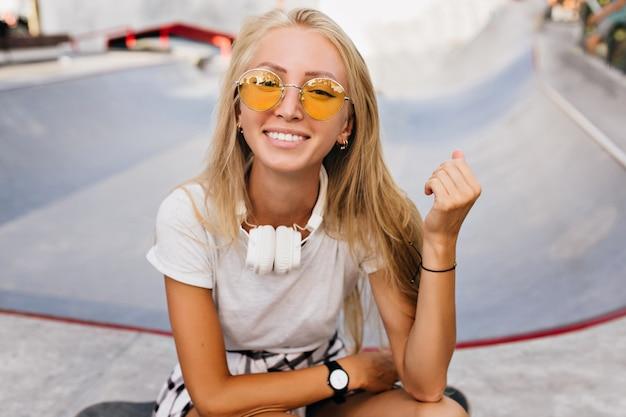 Mulher inspirada bronzeada em relógio de pulso moderno posando com um sorriso feliz. retrato ao ar livre de uma garota fascinante em grandes fones de ouvido, passando o tempo no parque de skate.
