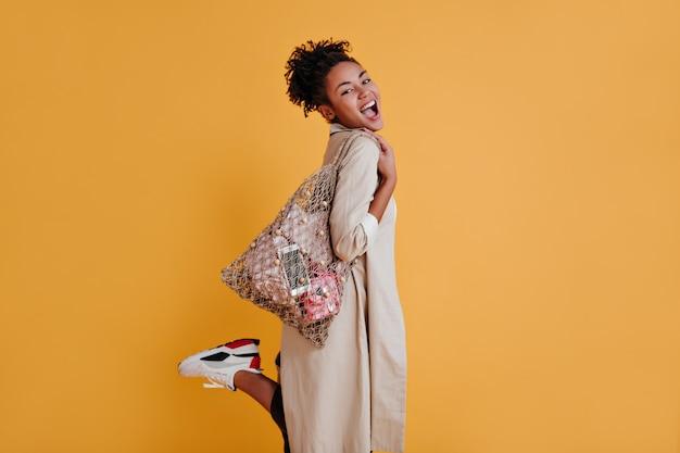 Mulher inspirada com bolsa de barbante apoiada em uma perna só