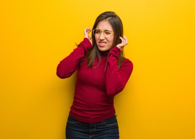 Mulher intelectual nova que cobre as orelhas com as mãos