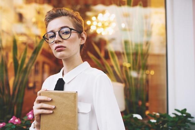 Mulher inteligente com cabelo curto segura o bloco de notas na mão e os óculos na janela externa do rosto