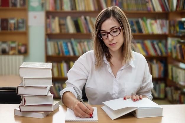 Mulher inteligente com óculos estudando na biblioteca no fundo das prateleiras com livros