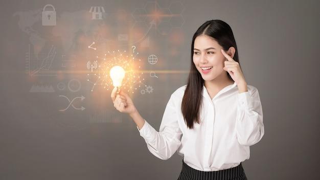 Mulher inteligente está segurando a lâmpada com dados comerciais e financeiros