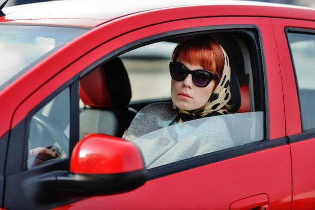 Mulher inteligente no carro vermelho