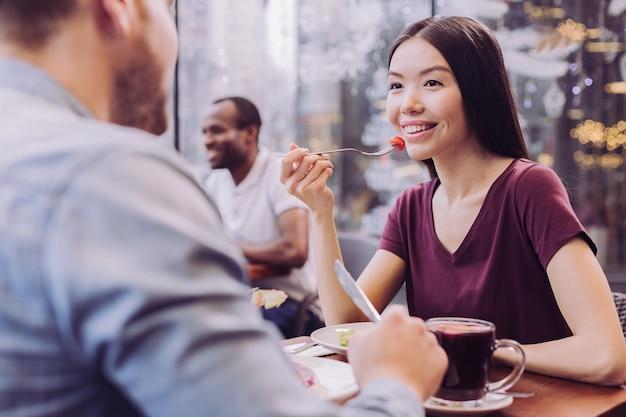 Mulher inteligente pensativa e alegre segurando o garfo enquanto olha para o homem e sorri