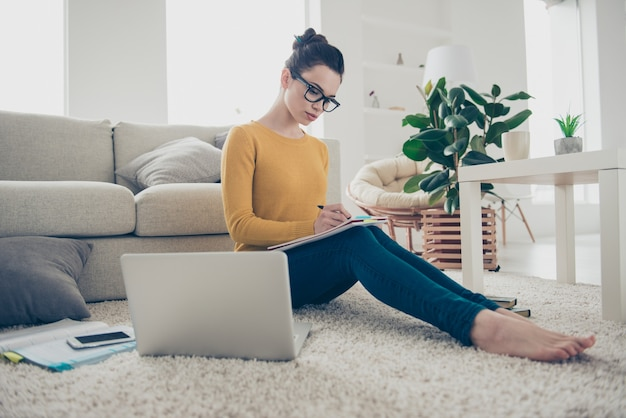 Mulher inteligente trabalhando em casa no chão