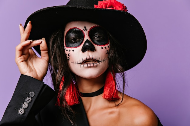 Mulher interessada com pintura de rosto assustador. retrato de halloween da menina morena latina com grande chapéu preto.
