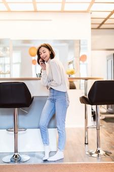 Mulher interessada com telefone em pé na cozinha panorâmica em roupas casuais