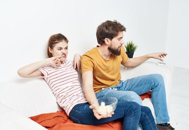Mulher interessada e homem barbudo sentam-se no sofá pipoca em um prato e flores em uma panela