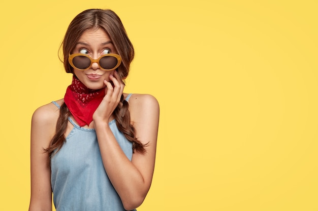Mulher intrigada e emotiva tem cabelos escuros penteados em duas tranças, usa óculos escuros, bandana, olha de lado com expressão curiosa, modelos sobre parede amarela com espaço livre para sua informação.