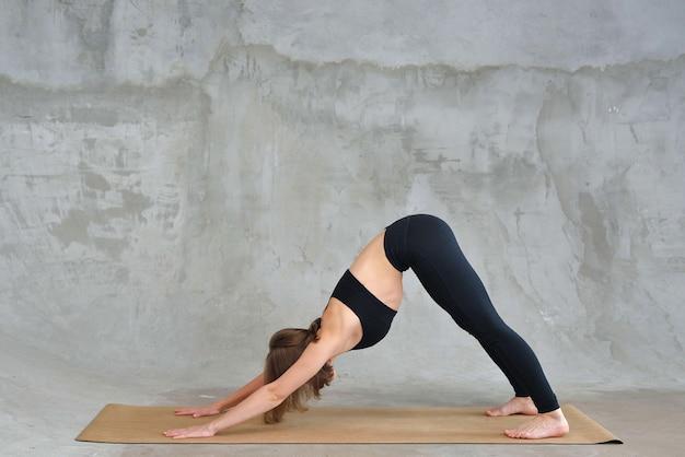 Mulher ioga, exercício de cão voltado para baixo, pose adho mukha svanasana, malhando