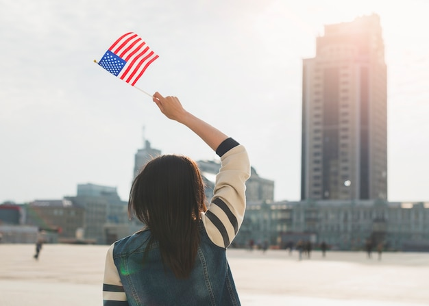 Mulher irreconhecível, acenando a bandeira americana no dia da independência