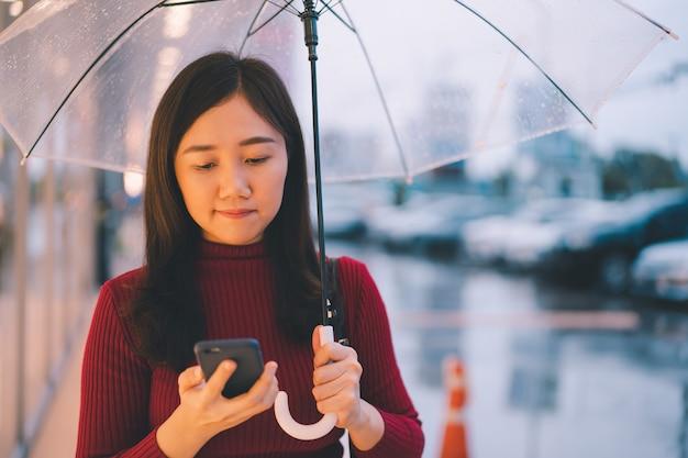 Mulher irreconhecível andando pela rua enquanto chovia, estrada de concreto úmida da tempestade