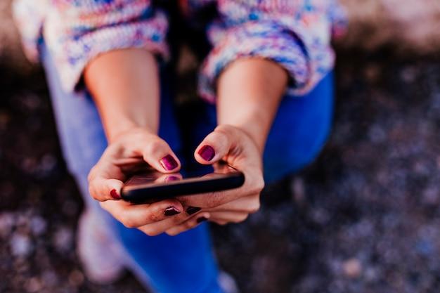 Mulher irreconhecível ao pôr do sol, usando telefone celular