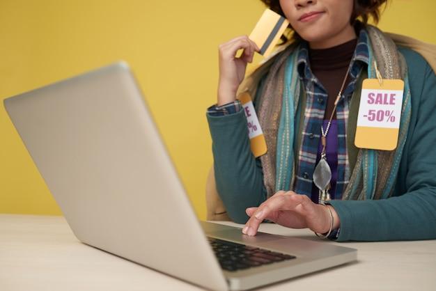 Mulher irreconhecível com cartão de crédito usando o laptop e usando cachecol com etiquetas de desconto