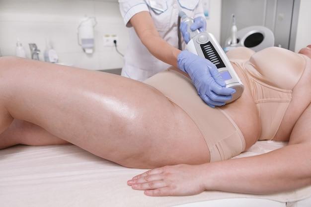 Mulher irreconhecível com excesso de peso recebendo massagem de endosferas abdominais por uma esteticista