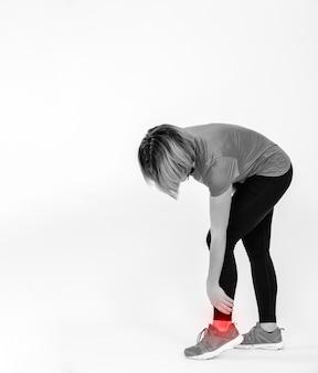 Mulher irreconhecível com tornozelo machucado