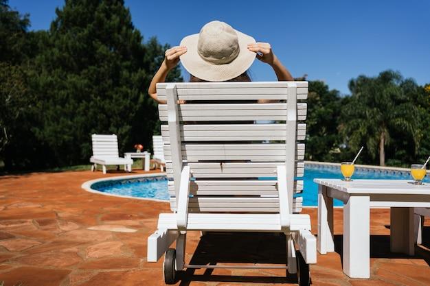 Mulher irreconhecível com um grande chapéu relaxante à beira da piscina.
