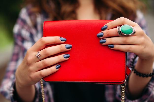 Mulher irreconhecível com unhas escuras, segurando a bolsa vermelha.