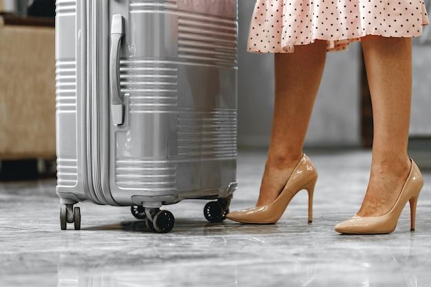 Mulher irreconhecível com vestido rosa em pé com mala de viagem perto