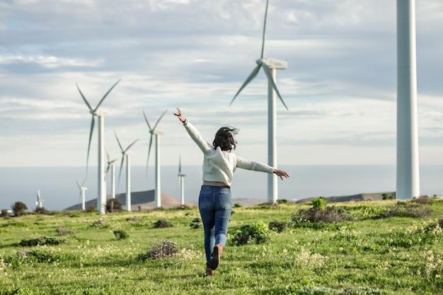 Mulher irreconhecível correndo em um prado com moinhos de vento