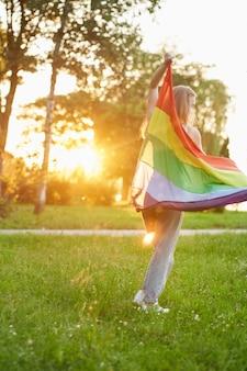 Mulher irreconhecível dançando com a bandeira lgbt nas costas