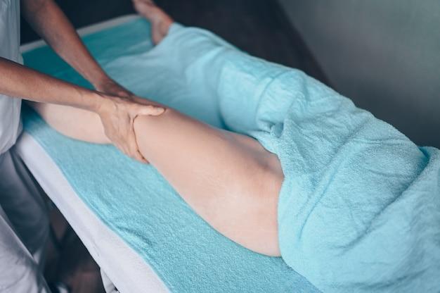 Mulher irreconhecível deitada na mesa de massagem e desfrutando da massagem terapêutica. terapeuta massagista de mãos fazendo massagem anticelulite na clínica de spa.