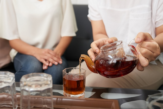 Mulher irreconhecível, derramando chá em copos