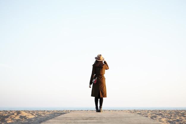 Mulher irreconhecível e elegante usando um chapéu elegante e um casaco preto longo