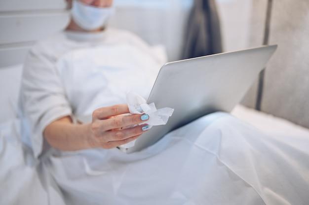 Mulher irreconhecível em máscara facial no quarto durante a quarentena de isolamento de coronavírus, limpando o laptop com desinfetante para as mãos, usando algodão com álcool para limpar, para evitar contaminação com covid-19