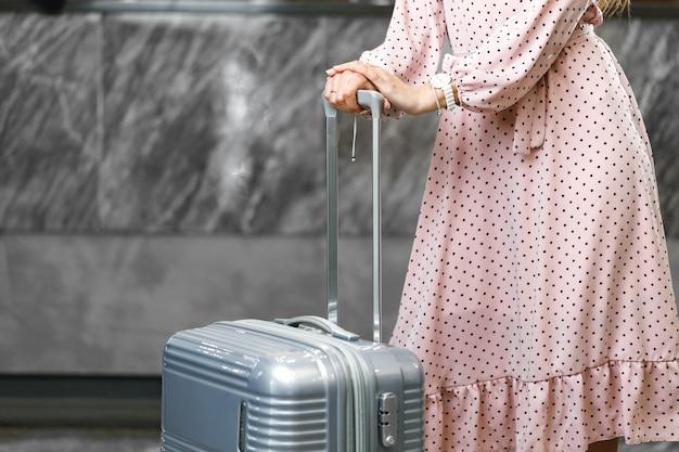 Mulher irreconhecível em vestido rosa em pé com mala de viagem close-up