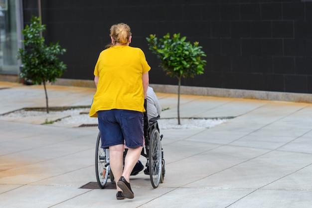 Mulher irreconhecível empurrando cadeira de rodas com uma pessoa com deficiência, vista traseira