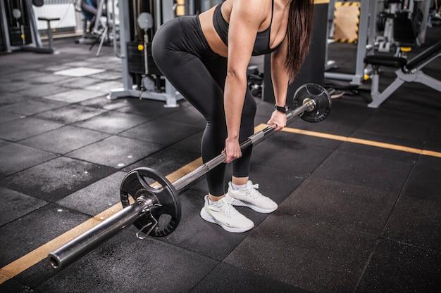 Mulher irreconhecível fazendo exercícios de levantamento terra com barra