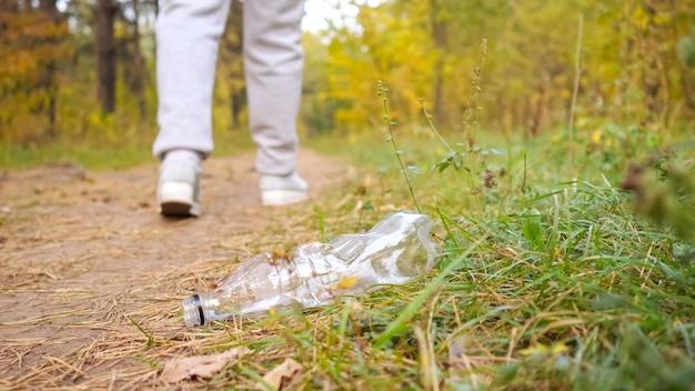 Mulher irreconhecível joga uma garrafa de plástico na grama da floresta.