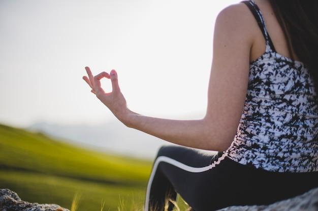 Mulher irreconhecível meditando sobre rock