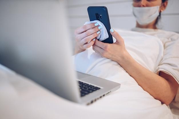 Mulher irreconhecível na máscara facial no quarto durante a quarentena de isolamento de coronavírus que limpa o telefone com um desinfetante para as mãos, usando algodão com álcool para limpar para evitar contaminação com covid-19