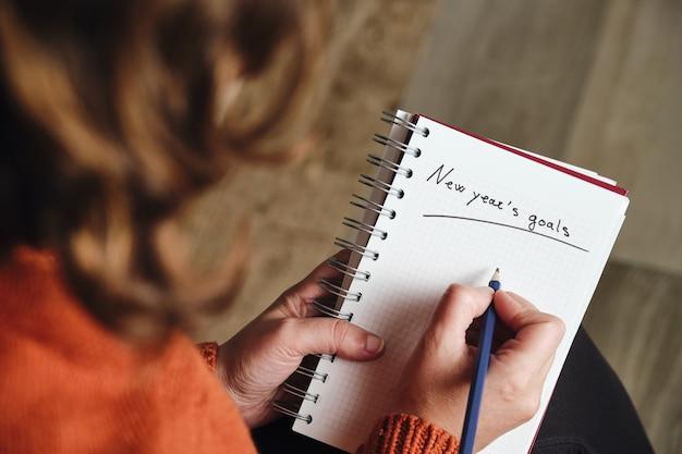 Mulher irreconhecível por trás, com um suéter laranja, segura um lápis e um caderno com as palavras metas de ano novo escritas.