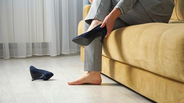 Mulher irreconhecível se senta no sofá e tira os sapatos de salto alto.