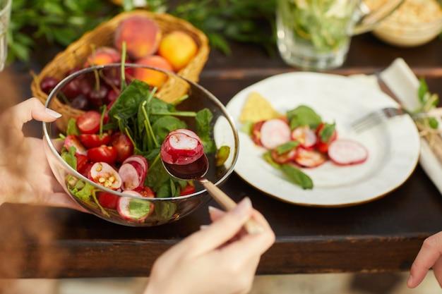 Mulher irreconhecível segurando salada de legumes fresca enquanto janta com amigos e família ao ar livre