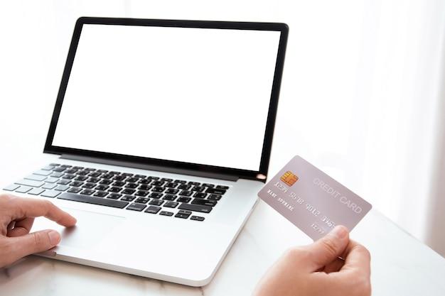 Mulher irreconhecível segurando um cartão de crédito na frente da tela do computador laptop, compras online e conceito de pagamento online seguro.