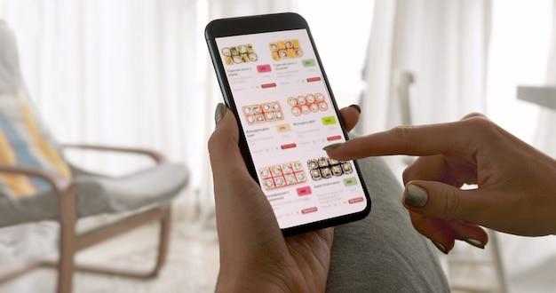 Mulher irreconhecível segurando um telefone com entrega de app de comida de sushi na tela em casa