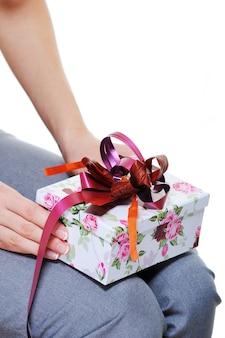 Mulher irreconhecível segurando uma caixa de presentes de joelhos