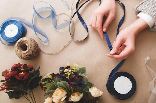 Mulher irreconhecível segurando uma fita azul na superfície bege com flores artificiais, rolos de fita e corda