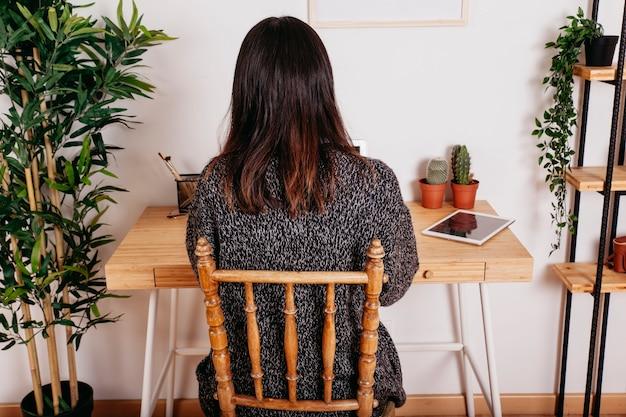 Mulher irreconhecível sentada no local de trabalho