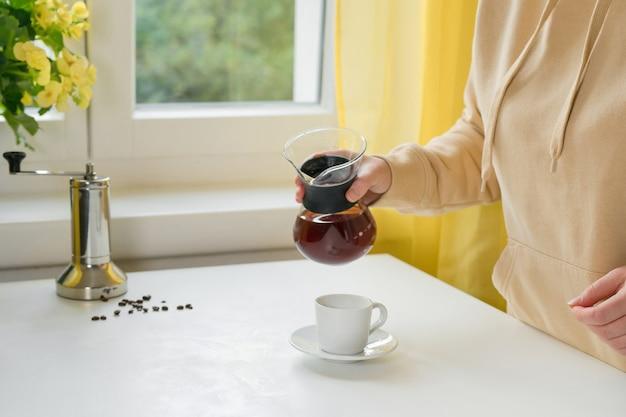 Mulher irreconhecível servindo café na cafeteira de vidro