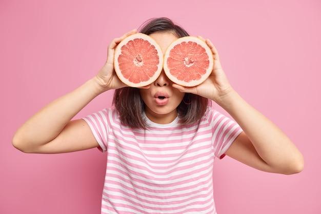 Mulher irreconhecível surpresa cobre os olhos com duas grandes metades de toranja, come comida saudável contendo muitas vitaminas e veste uma camiseta listrada isolada sobre a parede rosa tenta perder peso