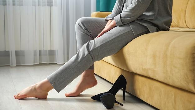 Mulher irreconhecível tira os sapatos e estica as pernas enquanto está sentada no sofá