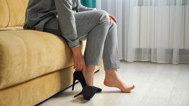 Mulher irreconhecível tira os sapatos e estica as pernas enquanto está sentada no sofá.