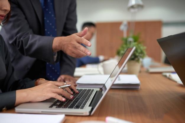 Mulher irreconhecível, trabalhando no laptop no escritório e homem em pé atrás, assistindo e apontando